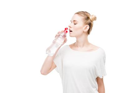 Aantrekkelijke jonge vrouw in wit t-shirt drinkwater uit de fles