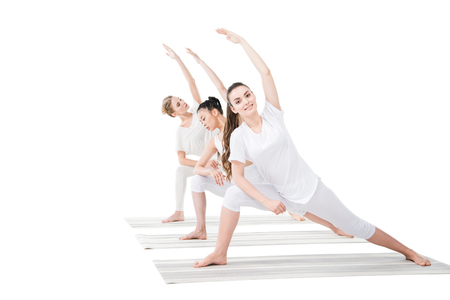 young women practicing Extended Side Angle Pose on yoga mats