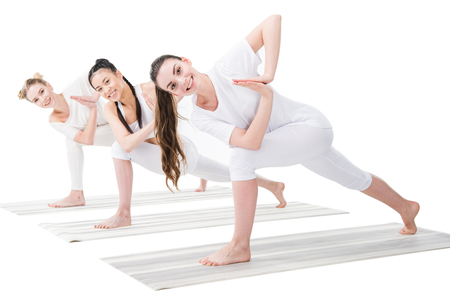 young women practicing variation of Revolved Side Angle Pose (Parivrtta Parsvakonasana) Imagens