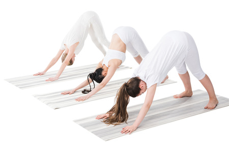 women performing yoga pose on yoga mats isolated on white
