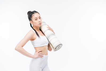 attractive asian girl in sportswear with yoga mat standing