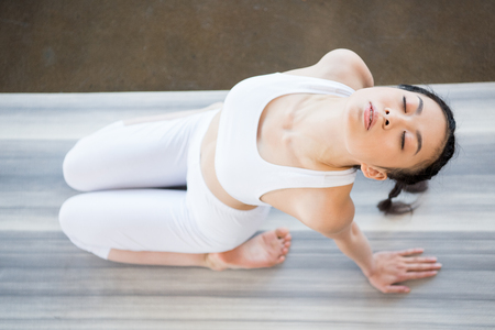 asian girl doing Yoga in backward bending pose with eyes closed Stock Photo