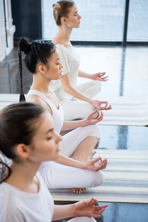 women with eyes closed meditating in lotus pose with gyan mudra indoors