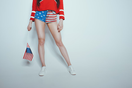 Low section of stylish hipster girl in american patriotic outfit isolated on grey, american culture concept
