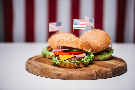 Three cheeseburgers with little american flags on wooden board, us flag on background, american culture concept