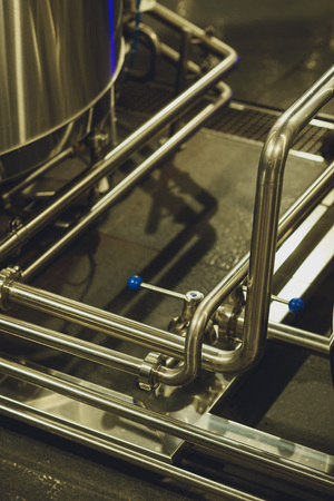 Modern brewery equipment with pipes for giving of malt and water