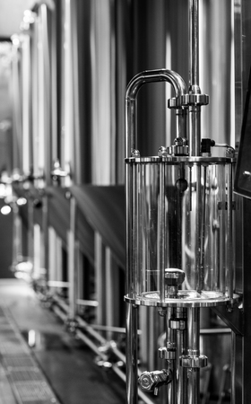 Black and white photo of modern brewery equipment with stainless tanks for the fermentation beer Stock Photo