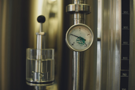 Close-up view of modern brewery equipment with gauge Stock Photo