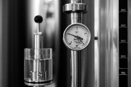 Close-up view of modern brewery equipment with gauge, black and white photo Stock Photo
