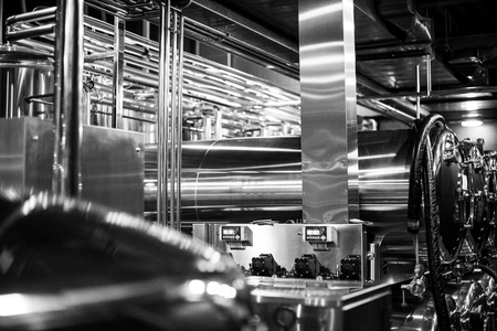 Black and white photo of modern brewery equipment with pipes and fermenting tanks Stock Photo