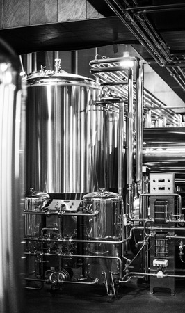 Black and white photo of modern brewery equipment with pipes and fermenting tank