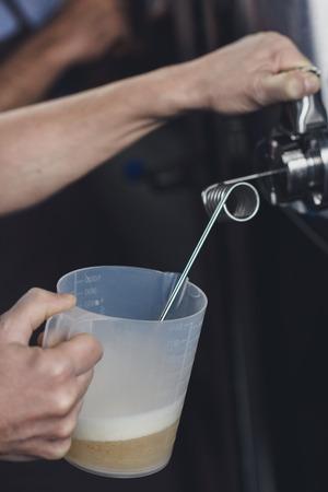 Handen van brouwerijarbeider die bier van de tank gieten aan plastikwaterkruik Stockfoto - 82184937