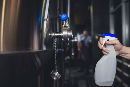 Hand of male worker spraying brewery equipment