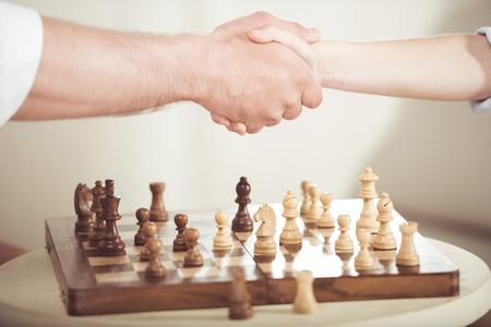 gedeeltelijke weergave van vader en zoon handen schudden na het spelen van schaakbordspel Stockfoto