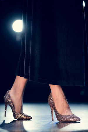 high section: low section of stylish glamour woman walking in glitter high heels and long black dress