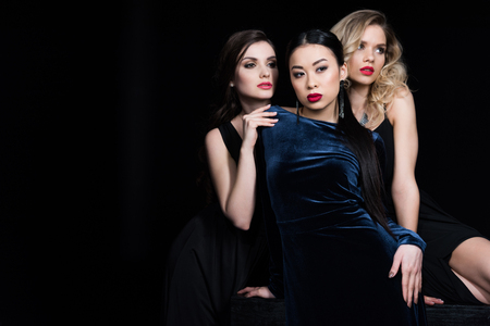 glamorous multiethnic women posing at dark evening gowns