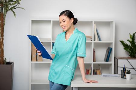asian internist holding clipboard with diagnosis and standing in clinic