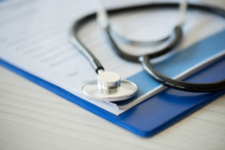stethoscope lying on clipboard with diagnosis, selective focus