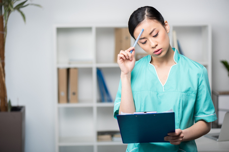 asian internist looking at clipboard with diagnosis in professional clinic Stock Photo
