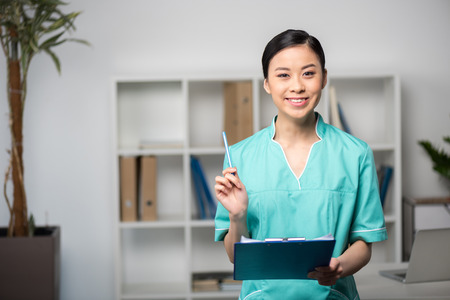 asian internist holding pen and clipboard with diagnosis in professional clinic