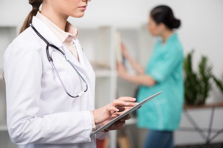 cropped view of doctor wearing white coat and using digital tablet