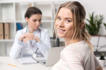 beautiful young patient smiling at camera and doctor using laptop behind