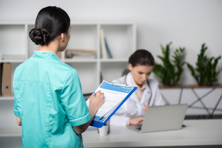 internist holding clipboard with diagnosis and looking at doctor sitting behind Stock Photo