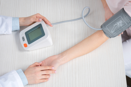 doctor measuring blood pressure to patient sitting at table