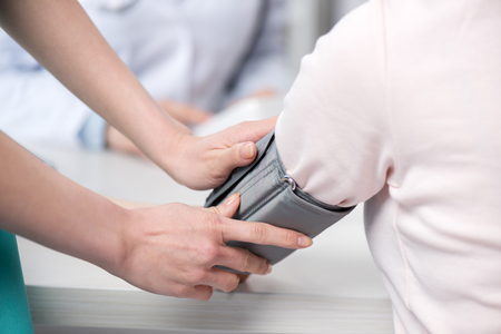 cuff: nurse putting blood pressure cuff to patient Stock Photo