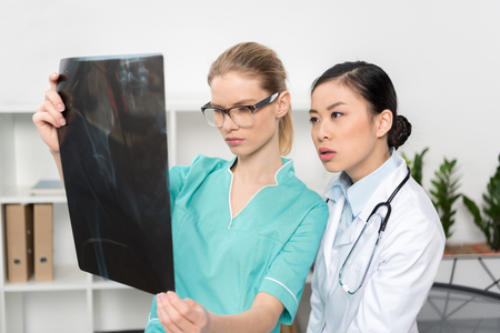 focused doctors looking at x-ray picture together at hospital