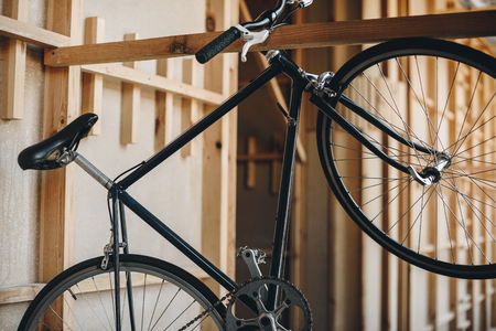classic black hipster bicycle hanging on wooden plank