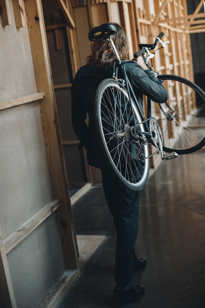 stylish young man with long hair walking and carrying bicycle on shoulder