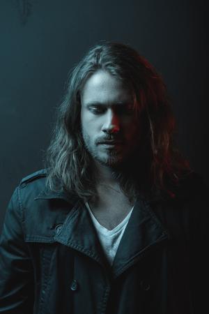 스튜디오에서 아래를 내려다 보면서 긴 머리를 가진 잘 생긴 세련된 수염 난 젊은이