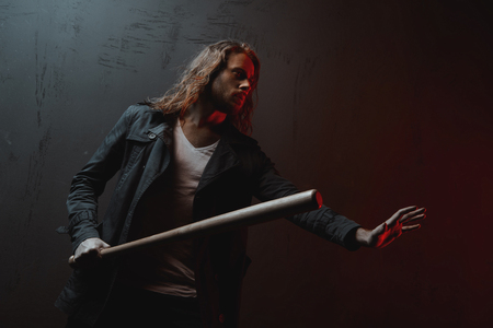 long haired man holding baseball bat ready to hit in darkness