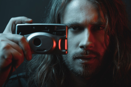 bearded young long haired man holding digital camera