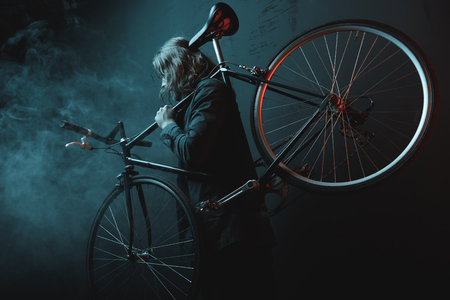 young long haired man carrying bicycle in dark studio Stock Photo - 82192780