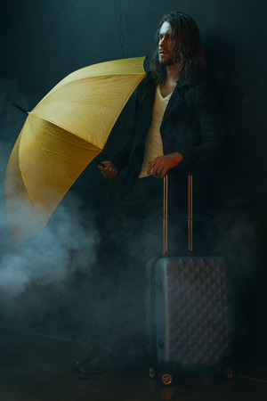 young long haired man holding yellow umbrella and suitcase