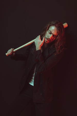 young long haired man holding baseball bat and touching chin in studio