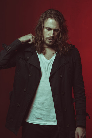 stylish long haired man posing in studio Stok Fotoğraf