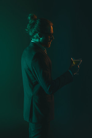young man in tuxedo holding glass with cocktail