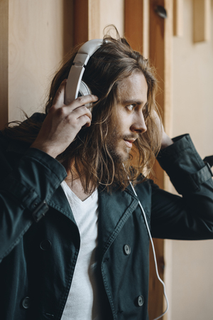 handsome stylish young man listening music in headphones