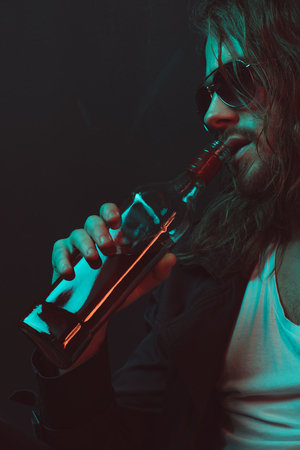 caucasian drunkard in sunglasses drinking whiskey from bottle