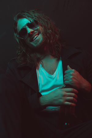 Lächelnder kaukasischer Mann in der Sonnenbrille , die Flasche mit Alkohol hält Standard-Bild - 82192302