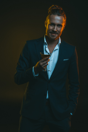 stylish man in tuxedo holding glass with cocktail