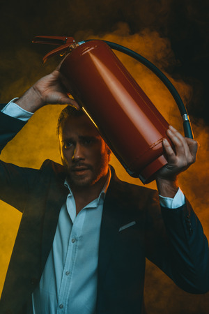 fireman: caucasian man in suit holding fire extinguisher Stock Photo