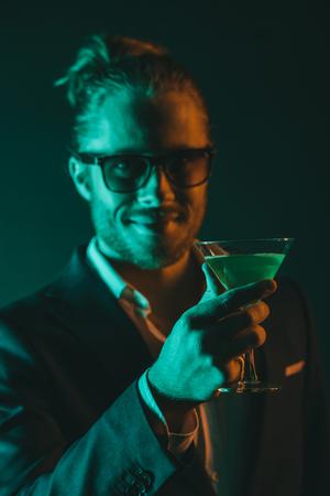 カクテルでガラスを保持している笑みを浮かべて青年