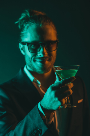 dinner jacket: young smiling man holding glass with cocktail