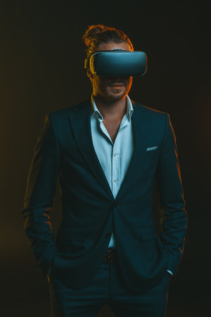 man in suit using virtual reality headset Stock Photo