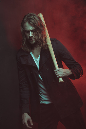 long haired man holding baseball bat on shoulder and looking down