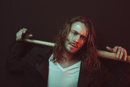 serious stylish long haired man holding baseball bat on shoulders and looking at camera